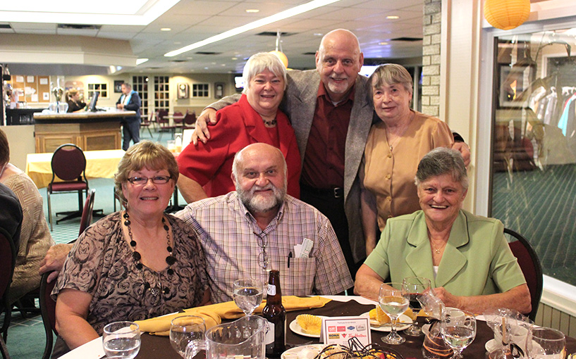 group of older people sitting posing for photo and looking at camera around a table