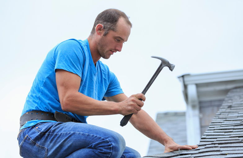 man on roof applying shingles with hammer