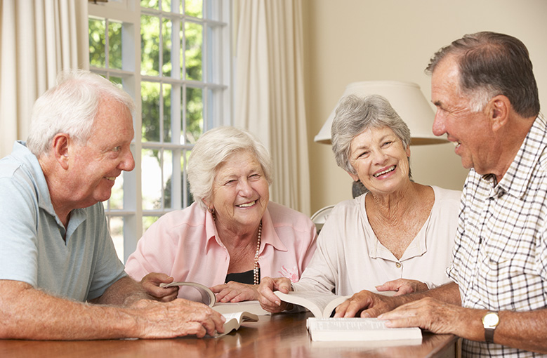 four seniors studying together with books