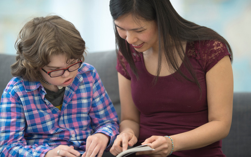 Young lady looking at a book with a boy