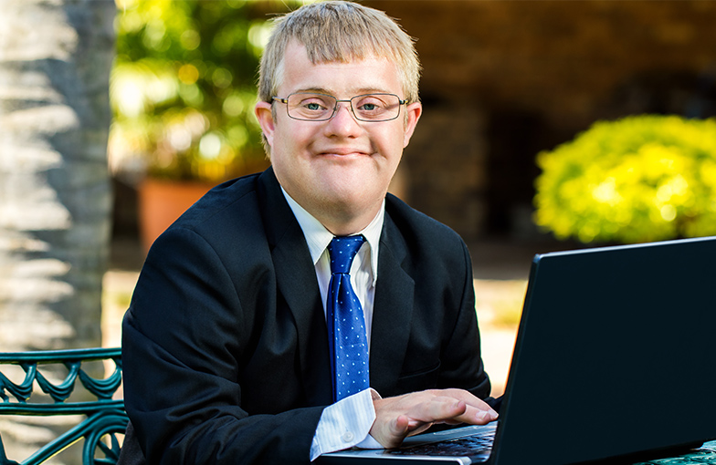Man with Down syndrome in a suit working on a lap top computer