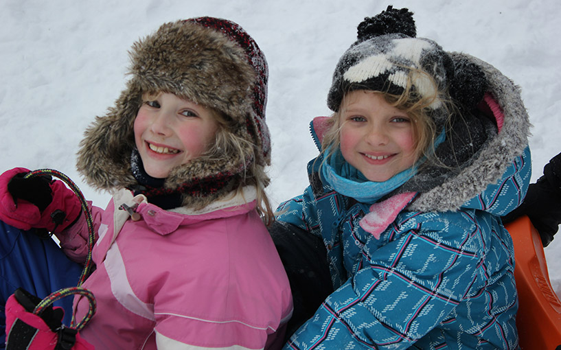 two young girls sitting on a sled in the snow