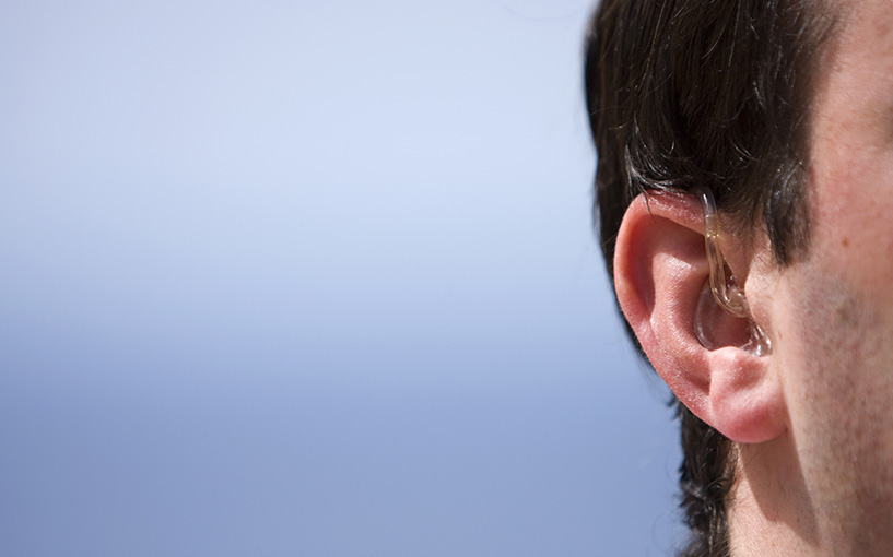 Hearing aid in man's ear