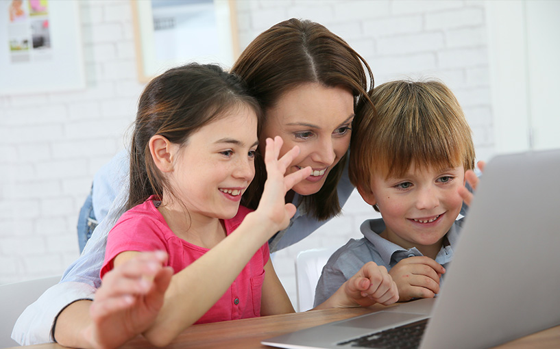 A woman with a small boy and small girl sitting at a laptop computer