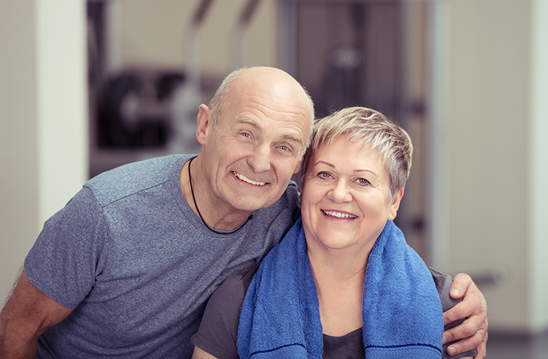 senior couple in active wear smiling at camera